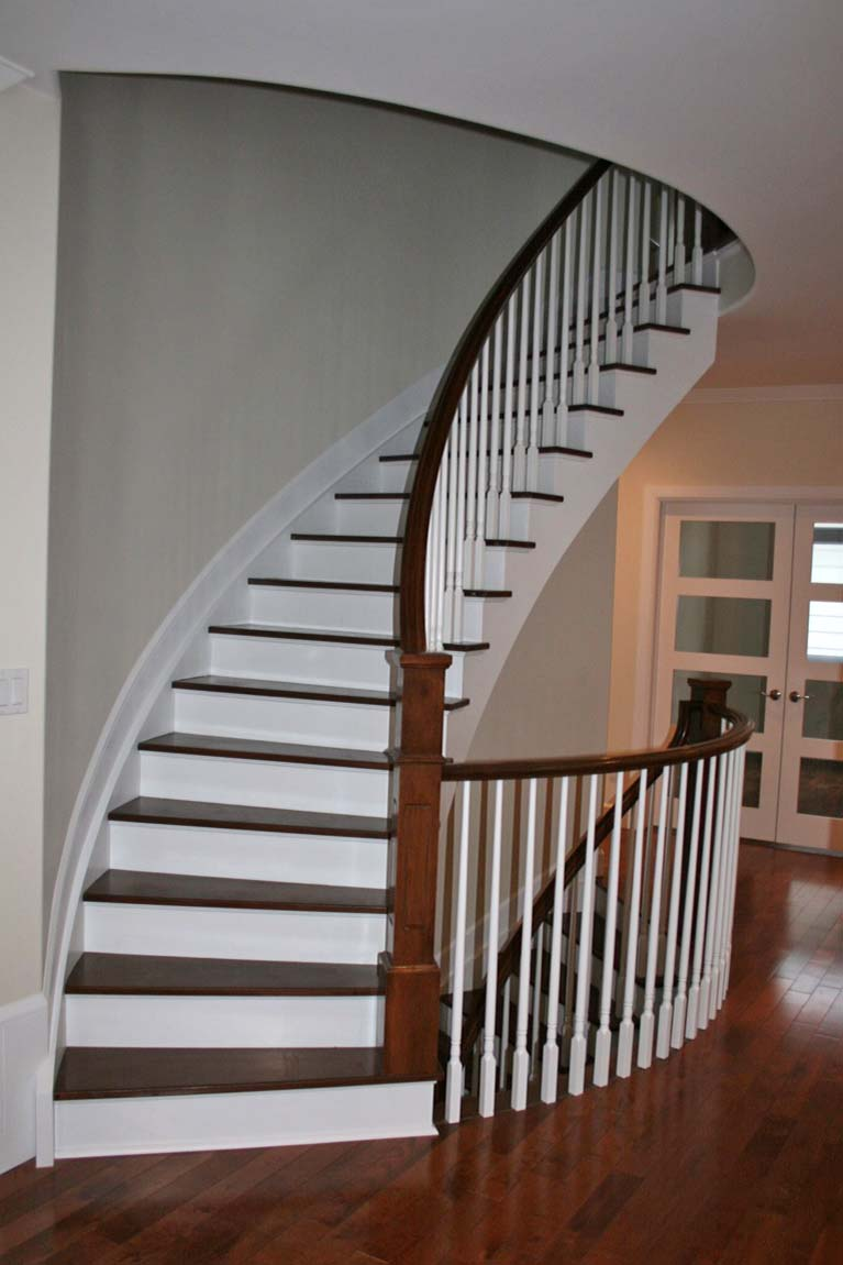Curved paint grade custom stairs with hardwood tread